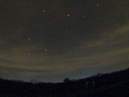 Výřez zjasnění nad obzorem v souhvězdí Herkula a domnělá slabá stopa bolidu a stromy.