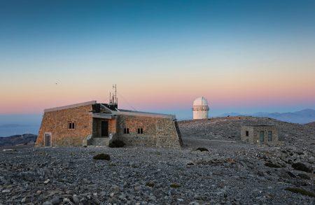 Pohled na správní budovu a kopuli 1,3m teleskopu, v pozadí pohoří Spathi s nejvyššími kopci kolem 2100 m n. m.
