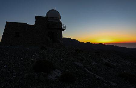 Západ Slunce s budovou 0,3m dalekohledu. Vpravo vedle kopule nejvyšší hora Kréty Psiloritis 2456 m n. m.