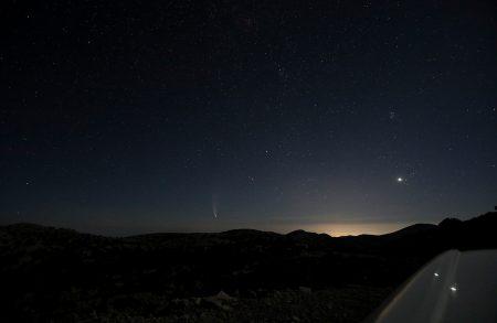 Širokoúhlý záběr foťákem položeným na střechu auta – kometa vlevo, vpravo Venuše v Hyadách, nad ní Plejády