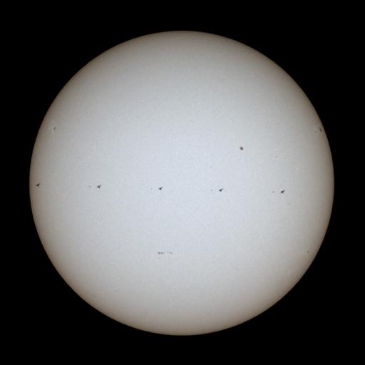 ISS a STS 135 Atlantis vedle sebe na slunečním disku se skvrnami.