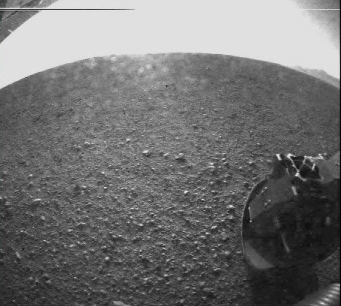 Třetí snímek z Marsu přijatý z Curiosity. Krytka navigační kamery už byla odklopena, vidíme tedy poměrně detailně rovnou pláň uvnitř kráteru Gale, jehož okraj je patrně v pozadí na snímku nahoře vpravo. NASA/JPL