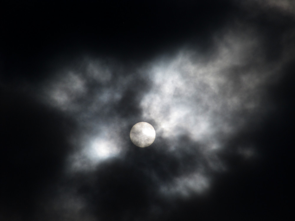 Slunce za mraky s velkou skvrnou na povrchu